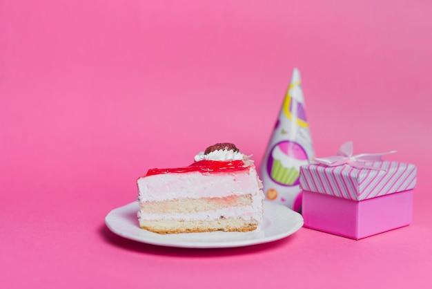Tranche de gâteau sur plaque avec chapeau de fête et coffret sur fond rose Photo gratuit