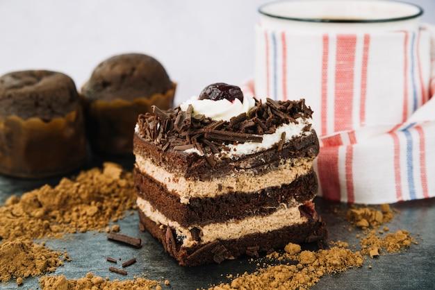 Tranche de gâteau avec de la poudre de cacao et une tasse de café Photo gratuit
