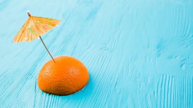 Tranche d'orange fraîche avec parapluie décoratif Photo gratuit