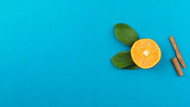 Tranche d'orange fraîche près de la cannelle et du feuillage Photo gratuit