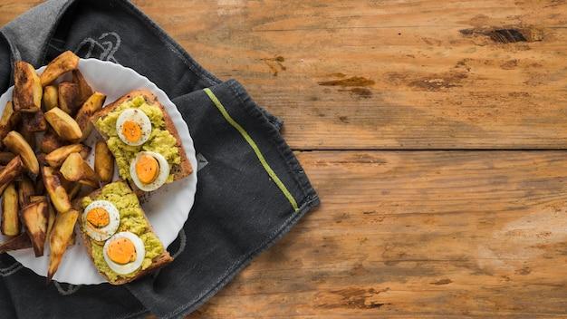 Tranche de pain grillé avec œuf à la coque et morceaux de pain grillé en assiette Photo gratuit