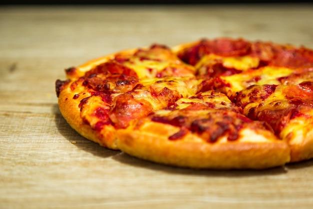 Tranche de pizza chaude avec du fromage fondant sur une table dans un restaurant italien de pizza. Photo Premium