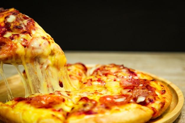 Tranche de pizza très au fromage à la main. tranche de pizza chaude avec du fromage fondant Photo Premium