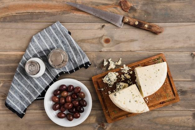 Tranche de roquefort; olives avec salière et poivrière sur table en bois Photo gratuit