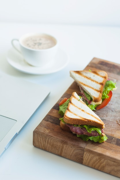 Tranche de sandwich au jambon et tasse de café sur le fond Photo gratuit