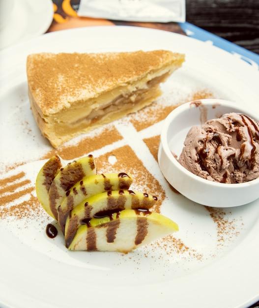 Une tranche de tarte aux pommes avec glace au chocolat, cannelle sur le dessus. Photo gratuit