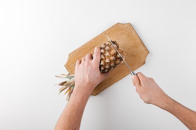 Trancher Des Ananas Avec Un Couteau Sur Un Plateau De Cuisine Photo Premium
