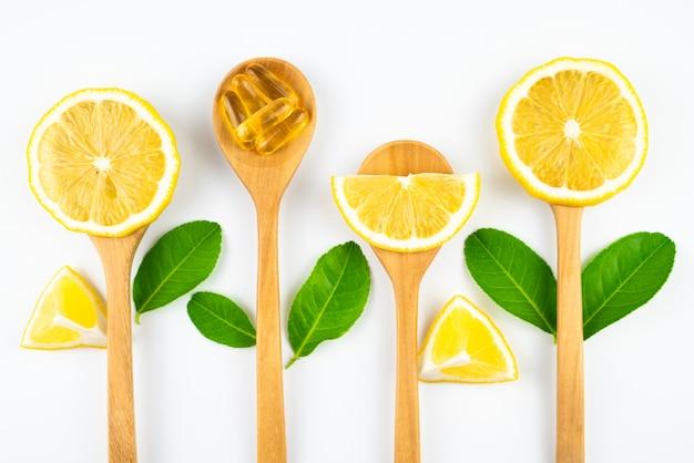 Trancher une capsule de citron et de vitamine c dans des suppléments de cuillère en bois pour une bonne santé, un concept de médecine et de médicaments Photo Premium