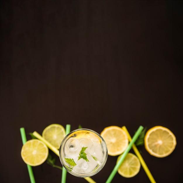 Tranches d'agrumes près d'un verre de boisson avec de la glace Photo gratuit