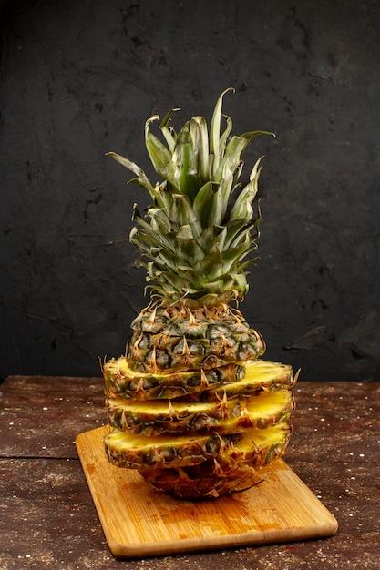 Tranches D'ananas Moelleux Mûrs Juteux Magnifiquement Conçus Sur Un Bureau Brun Et Un Plancher En Bois Photo gratuit