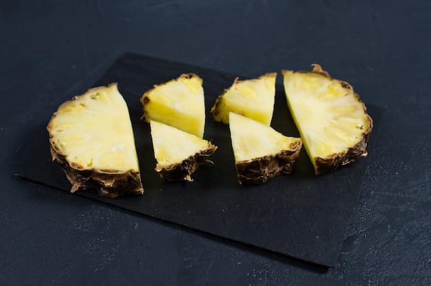 Tranches d'ananas sur un tableau de pierre noire avec un espace pour le texte Photo Premium