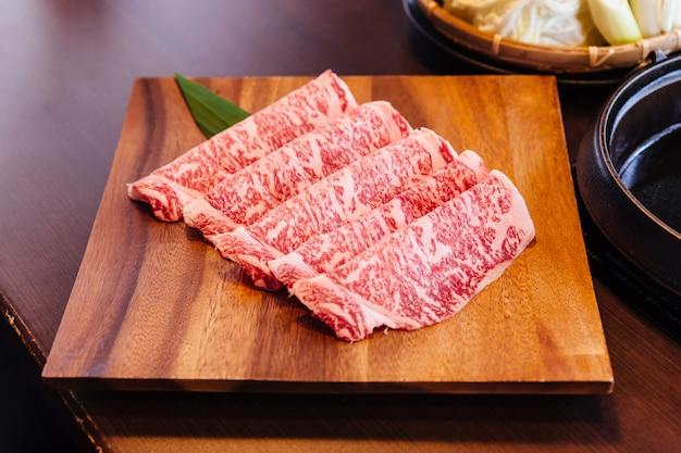Tranches de boeuf rares de première qualité wagyu a5 à la texture marbrée élevée servies pour sukiyaki et shabu. Photo Premium