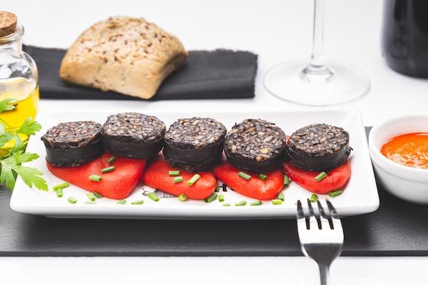 Tranches De Boudin Noir Espagnol Sur Les Poivrons Piquillo En Plaque Blanche Sur La Surface Blanche Photo Premium