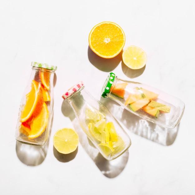 Tranches de bouteilles d'orange et de verre avec des agrumes coupés Photo gratuit