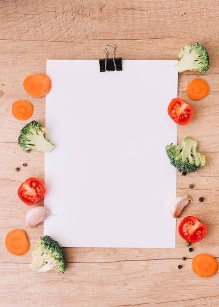 Tranches de carotte; brocoli coupé en deux; tomates; gousse d'ail et poivre noir sur le côté d'un papier blanc vierge sur le bureau en bois Photo gratuit