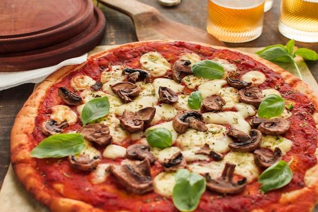Tranches de champignons et feuilles de basilic sur une pizza à la sauce tomate Photo gratuit