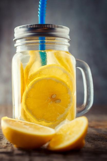 Tranches de citron dans un bocal avec de l'eau et un tube bleu Photo Premium