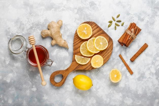 Tranches de citron sur une planche à découper, bâtons de cannelle, miel sur du béton. vue de dessus, espace de copie Photo gratuit
