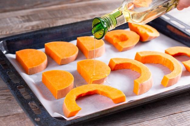 Tranches De Citrouille Brillantes Préparées Pour La Cuisson Au Four Avec De L'huile D'olive, Ingrédient Alimentaire Photo Premium