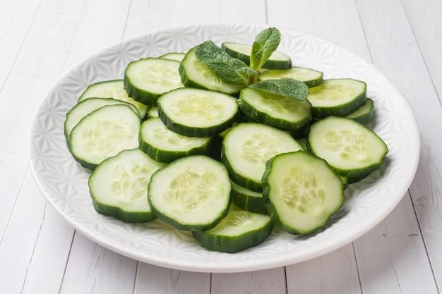 Tranches de concombre à la menthe sur une assiette. régime de concept. Photo Premium