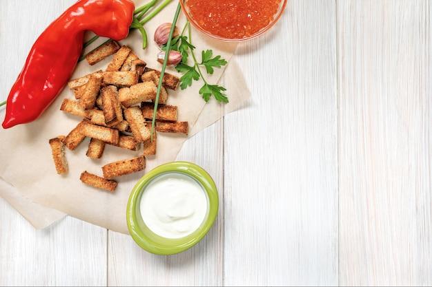 Tranches De Croûtons Frits Avec Sauce à La Crème Sure, Poivron Rouge, Caviar Et Gousses D'ail Sur Une Planche De Bois Blanc Photo Premium