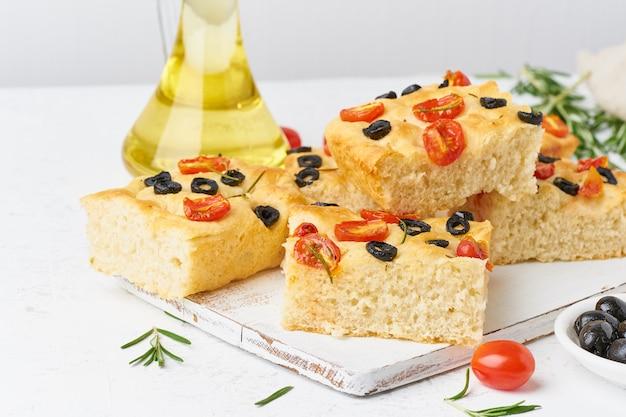 Tranches de focaccia à la tomate, aux olives et au romarin. copier l'espace pour le texte. Photo Premium
