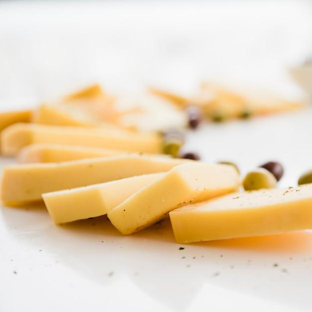 Tranches de fromage frais aux olives sur un bureau blanc Photo gratuit