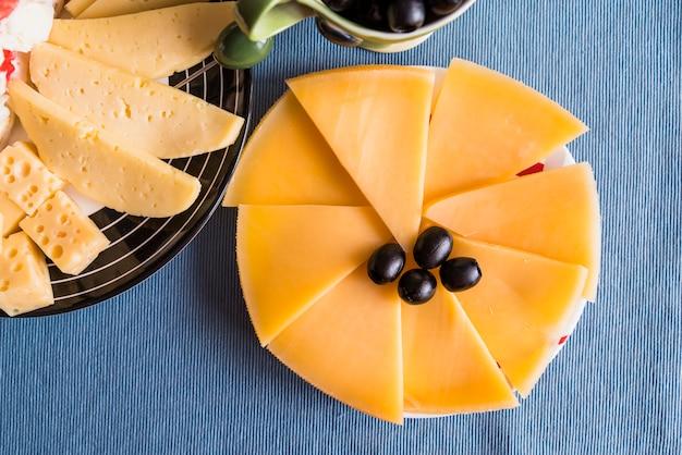 Tranches de fromage frais et des olives sur des assiettes Photo gratuit