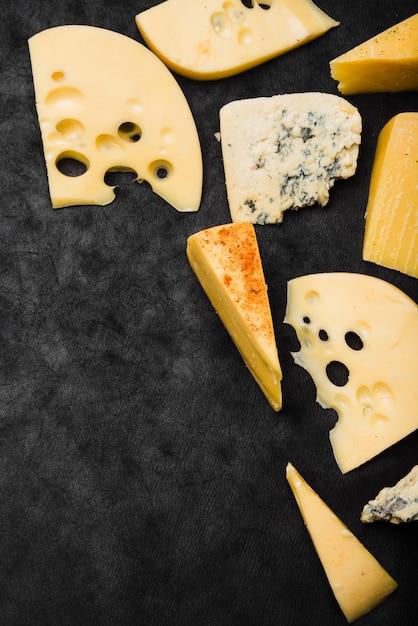 Tranches de fromage et tranches de fromage sur un plan de travail de cuisine noir Photo gratuit