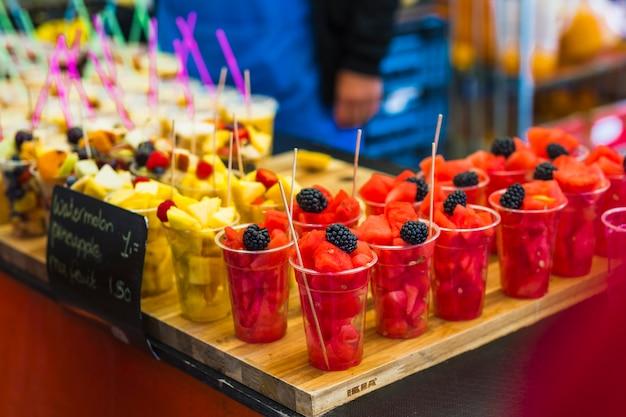 Tranches de fruits frais dans le gobelet jetable en plastique à vendre Photo gratuit