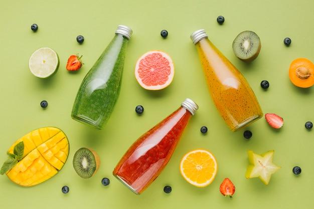 Tranches de fruits plats et bouteilles de jus Photo gratuit