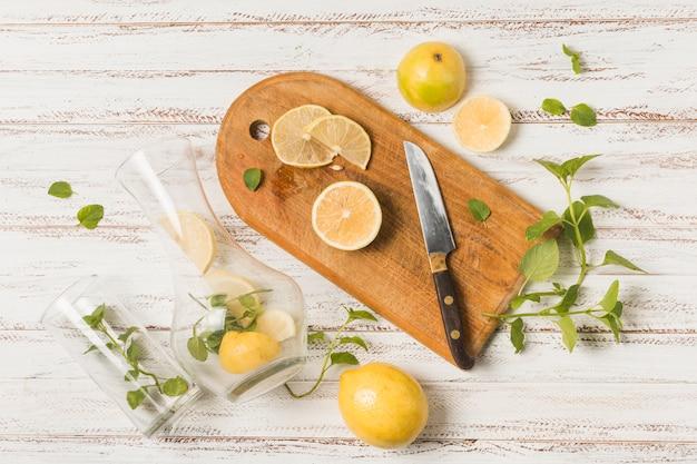 Tranches De Fruits Près Du Couteau Sur Une Planche à Découper Entre Des Herbes Et Des Verres Photo gratuit