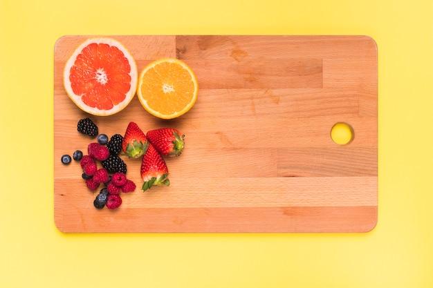 Tranches de jus d'orange citron orange fraise mûre framboise et cassis sur une planche à découper Photo gratuit