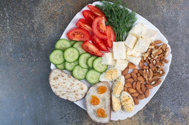 Tranches De Légumes, œufs, Fromage Et Noix Sur Plaque Blanche. Photo gratuit