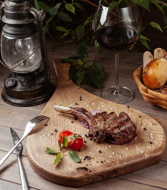 Tranches De Morceau De Steak D'agneau Sur Os Avec Des Paillettes De Sel De Mer, Sur Une Planche De Bois Photo gratuit