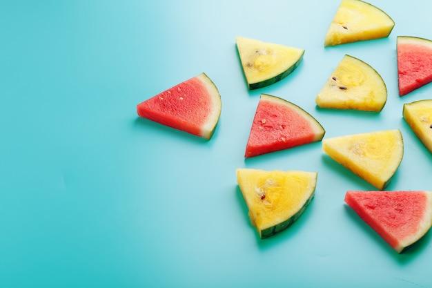 Tranches de morceaux frais de melon d'eau jaune et rouge sur bleu. Photo Premium
