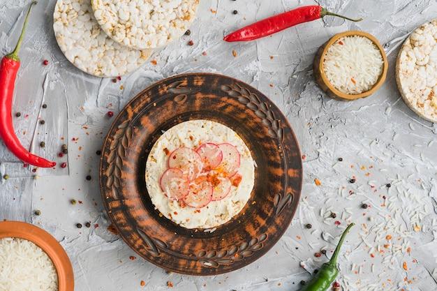 Tranches de navet sur des gâteaux de riz soufflés assaisonnés de piment rouge et de poivrons noirs sur fond de béton Photo gratuit