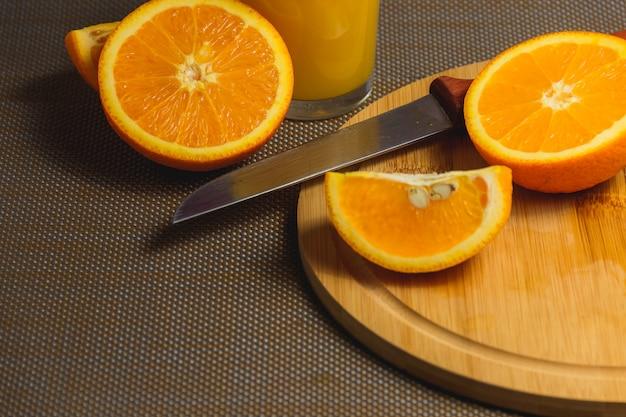 Tranches d'orange avec un couteau sur une planche à découper en bois Photo Premium