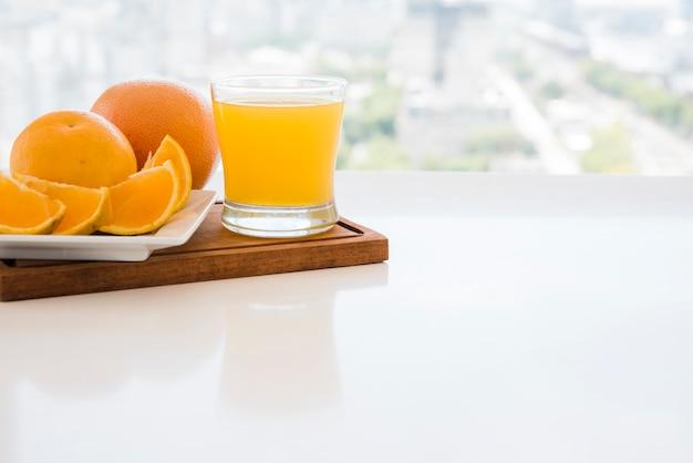 Tranches d'orange et jus sur une planche à découper sur la table blanche Photo gratuit