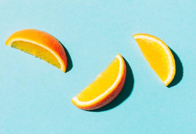Tranches d'orange vif posées sur une surface turquoise Photo gratuit