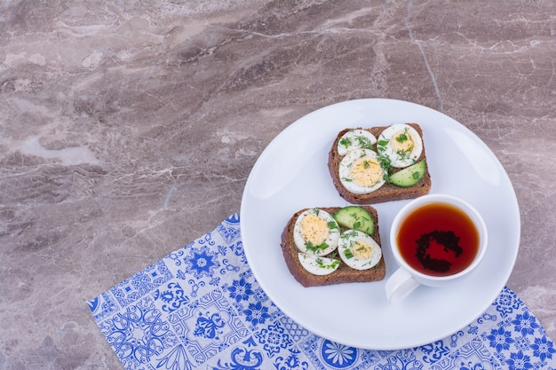 Tranches De Pain Aux Oeufs Et Herbes Servies Avec Une Tasse De Thé Photo gratuit