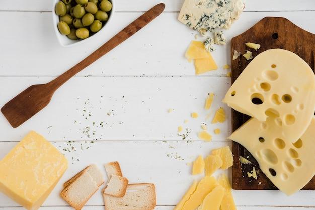 Tranches De Pain Aux Olives; Pain Et Fromage Sur Le Bureau Blanc Photo gratuit