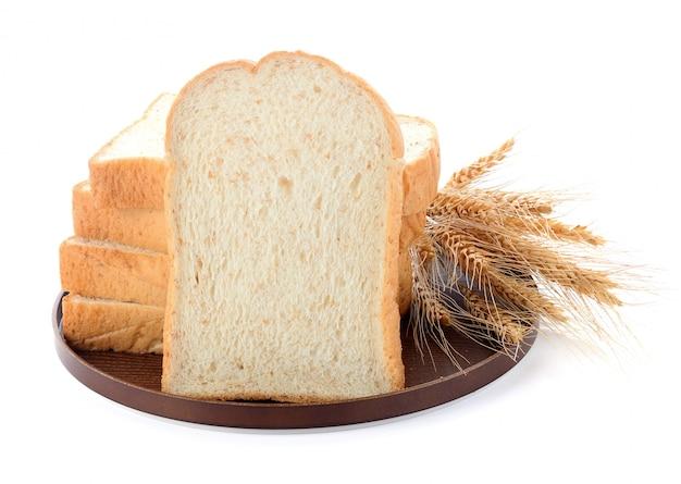 Tranches de pain et de blé sur une planche de bois isolé sur blanc Photo Premium