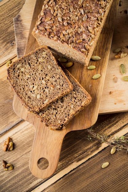 Tranches de pain brun entier aux graines de tournesol sur une planche à découper Photo gratuit