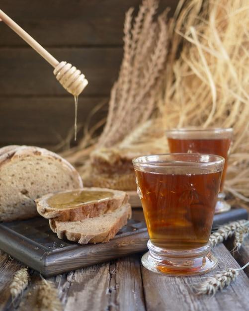 Des tranches de pain avec du miel et du thé dans des verres. fond de village Photo Premium