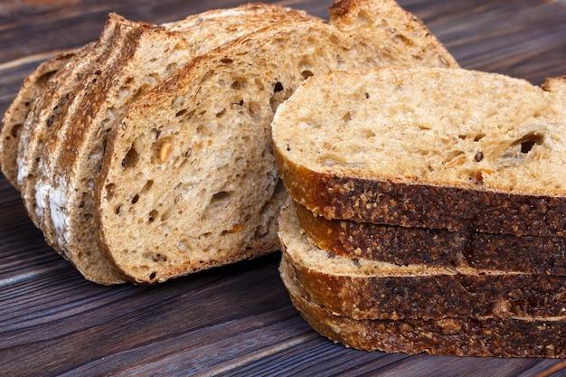 Tranches de pain frais sur une planche à découper sur un fond en bois blanc Photo Premium