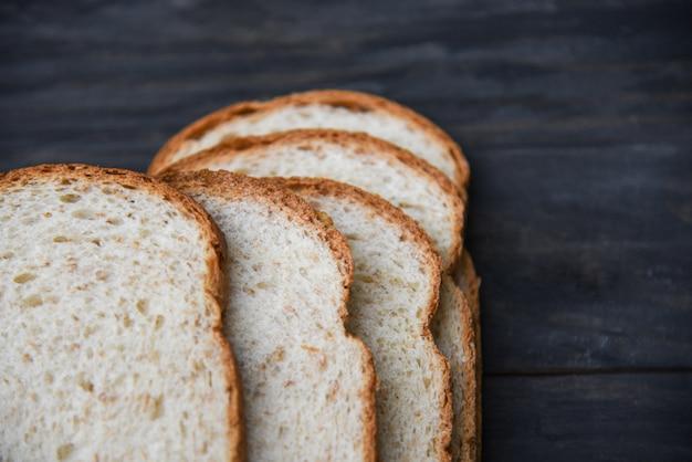 Tranches de pain gros plan vue de dessus - pain de blé entier coupé sur bois sombre Photo Premium