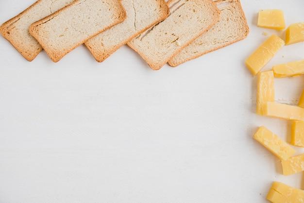 Tranches de pain avec une tranche de fromage cheddar sur fond blanc Photo gratuit