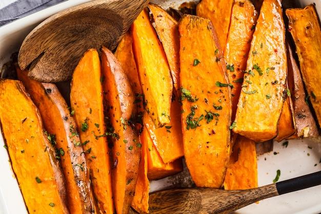 Tranches de patates douces cuites au four avec des épices dans un plat à four. concept de nourriture végétalienne saine. Photo Premium