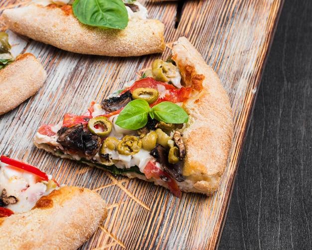 Tranches De Pizza à Angle élevé Sur Une Planche à Découper Photo gratuit